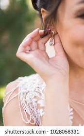 Bride puts on a gold earring in her ear. Delicate brunette touches her luxury earrings. Wedding details
