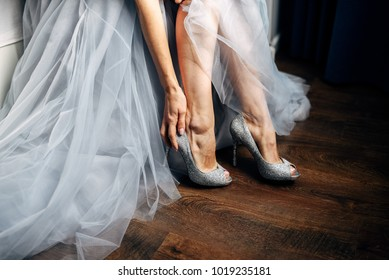 Bride puts on her silver wedding shoes, grey wedding dress on background