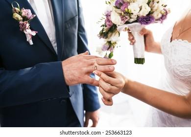 Bride puts on wedding ring on groom's finger