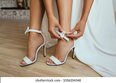 Bride puts on wedding shoes on her tender feet