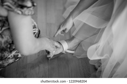 Bride puts on wedding shoes on her feet