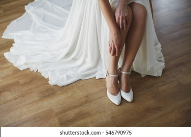bride puts on white shoes on feet