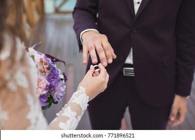 Bride puts ring on groom's finger.