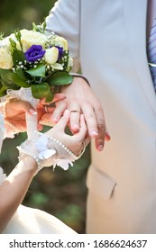 Bride puts wedding ring on the groom's finger