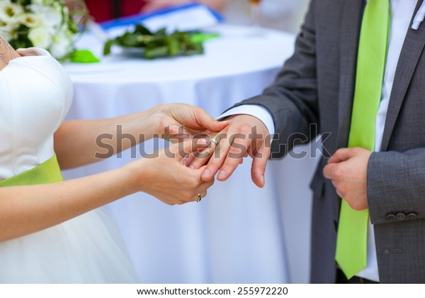 Bride puts a wedding ring on husband's finger. Stylish, beautifully dressed, green belt and tie.