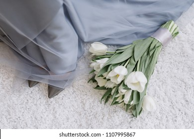 The bride is putting on her shoes, sitting on the armchair. Wedding morning. A girl in a blue dress demonstrates off her gray shoes. A bouquet of tulips.