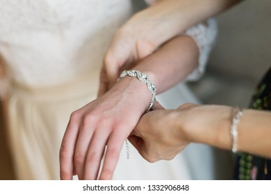 bride putting on luxury bracelet on hand in the morning, getting ready.