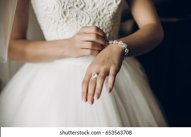 bride putting on luxury bracelet on hand in the morning, getting ready