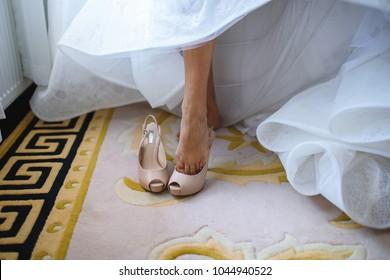 bride putting on wedding shoes on carpet