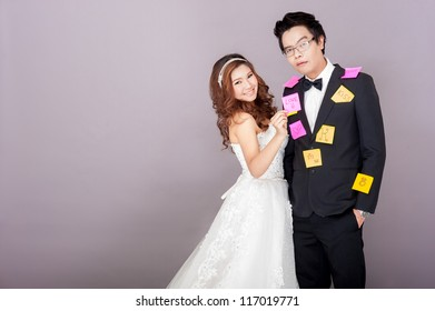 Bride putting post note on the groom with smile on her face while groom make his expression of confuse and surprise