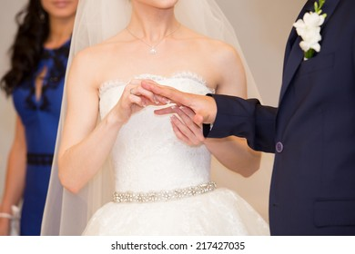 Bride putting a ring on groom hand