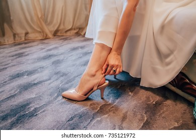 Bride is putting a shoe on her leg