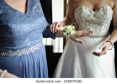 Bride Putting a White Floral Corsage on the Mother of the Bride Wearing an Ornate Wedding Gown