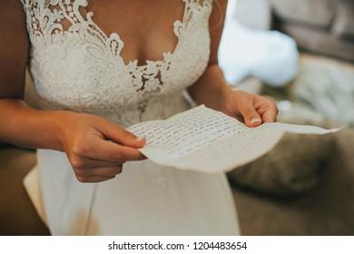 bride reading handwritten letter from groom on wedding day
