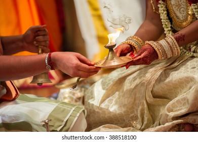Bride receiving lamp from priest at a Tamil Hindu wedding