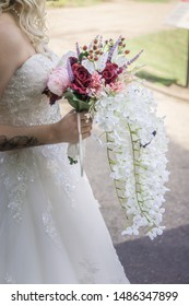 Bride with red white and pink trailing bouquet. Colchester, UK. 17.08.2019