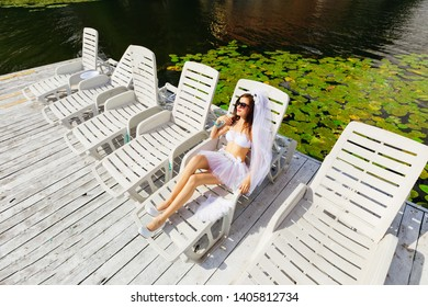 Bride resting on a sunbed near the lake. hen party. bride in bra, skirts and bridal veil