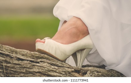 Bride rests her foot on tree trunk