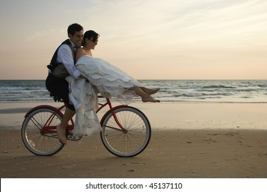 Bride rides the handle bars of a bicycle being driven by her groom on beach. Horizontal shot.