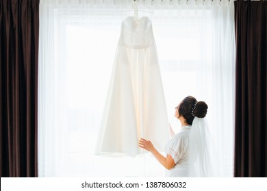 bride in a robe with bridal veil watching and touching the wedding dress on the background of the window