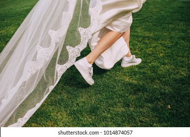 bride runs along the grass in a white long dress in sneakers