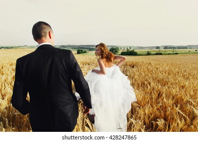 Bride runs away from a fiance crossing a golden field