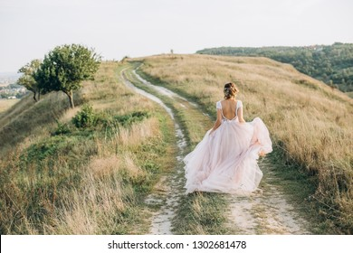 bride runs up the hill along the road and lifts the magnificent dress