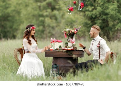 The bride in rustic style with a beautiful wreath on the head of flowers  in a park in white dress with groom white hair in white shirt suspenders sit at a table with wine sweets and a wedding cake