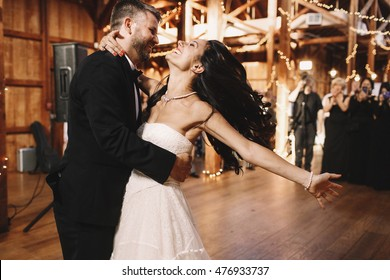 Bride shakes her dark hair while dancing with a groom in wooden hall