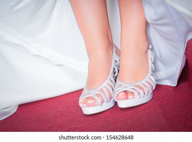 bride shoes and dress on a red carpet