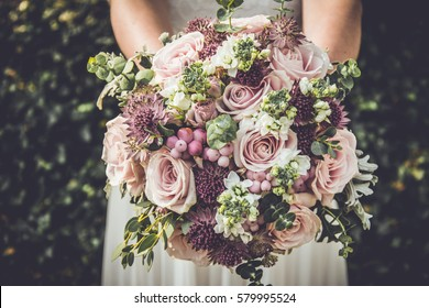 Bride showing off her beautiful boho flowers bouquet. Perfect image with copy space for: chic boho wedding magazines and websites, bohemian, fashion, florist and other related subjects.
