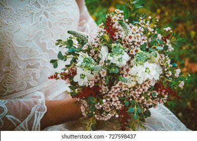 Bride showing off her beautiful boho flowers bouquet. Boho / vintage image with copy space for: amazing boho wedding flowers, bohemian dress, women fashion, florist and other related subjects.