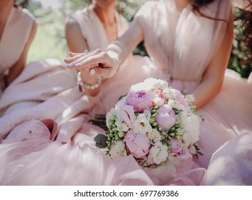 Bride shows to the bridesmaids her wedding ring