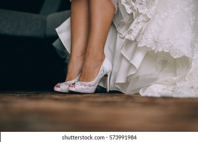 The bride shows white wedding shoes