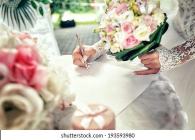 Bride signs up document on civil wedding ceremony.