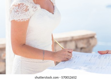 The bride signs on wedding ceremony above sea. Bride is dressed in white lace wedding dress.