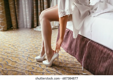 Bride in a silk robe with beautiful slim legs is putting on bridal shoes. Wedding morning preparation. Close-up