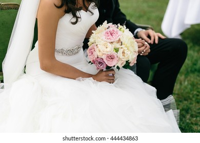 Bride sits with groom in the garden holding a wedding bouquet in her arm