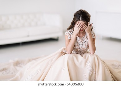 the bride sits in a white room and is sad. Natural light. covers your eyes