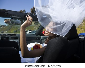 Bride sitting in a car while her wedding veil floating in the air