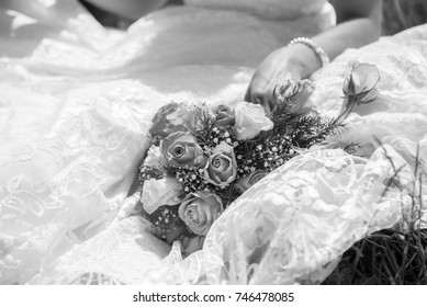 Bride sitting down with bouquet on her dress in black and white