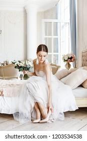 Bride sitting on bed puts on shoes