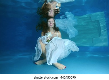 The bride sitting in a white dress under water at the bottom of the pool