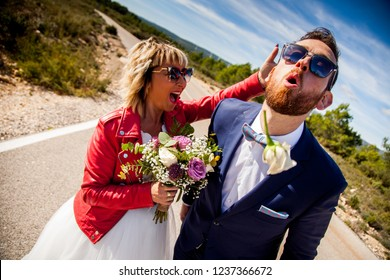 Bride slaps her boyfriend in the back of the head and he spits out a flower he was carrying in his mouth.
