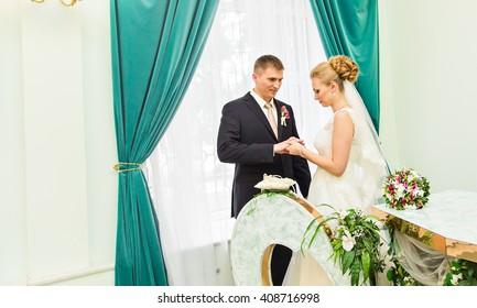 Bride slipping ring on finger of groom at wedding