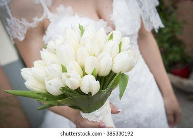 bride is standing with a bouquet in her hand
