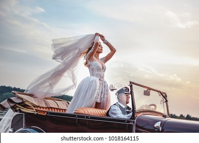 Bride standing in classic convertible while being driven by older driver