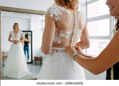 Bride is standing in front of mirror and fitting dress in atelier with wedding assistant. Woman with dressmaker are making final touch on tailor made gown in bridal clothing shop.