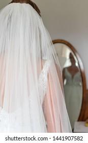 Bride standing in front of mirror. reflexing of bride in mirror