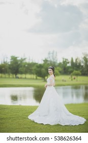 bride standing in a green grass field under a sunny sky